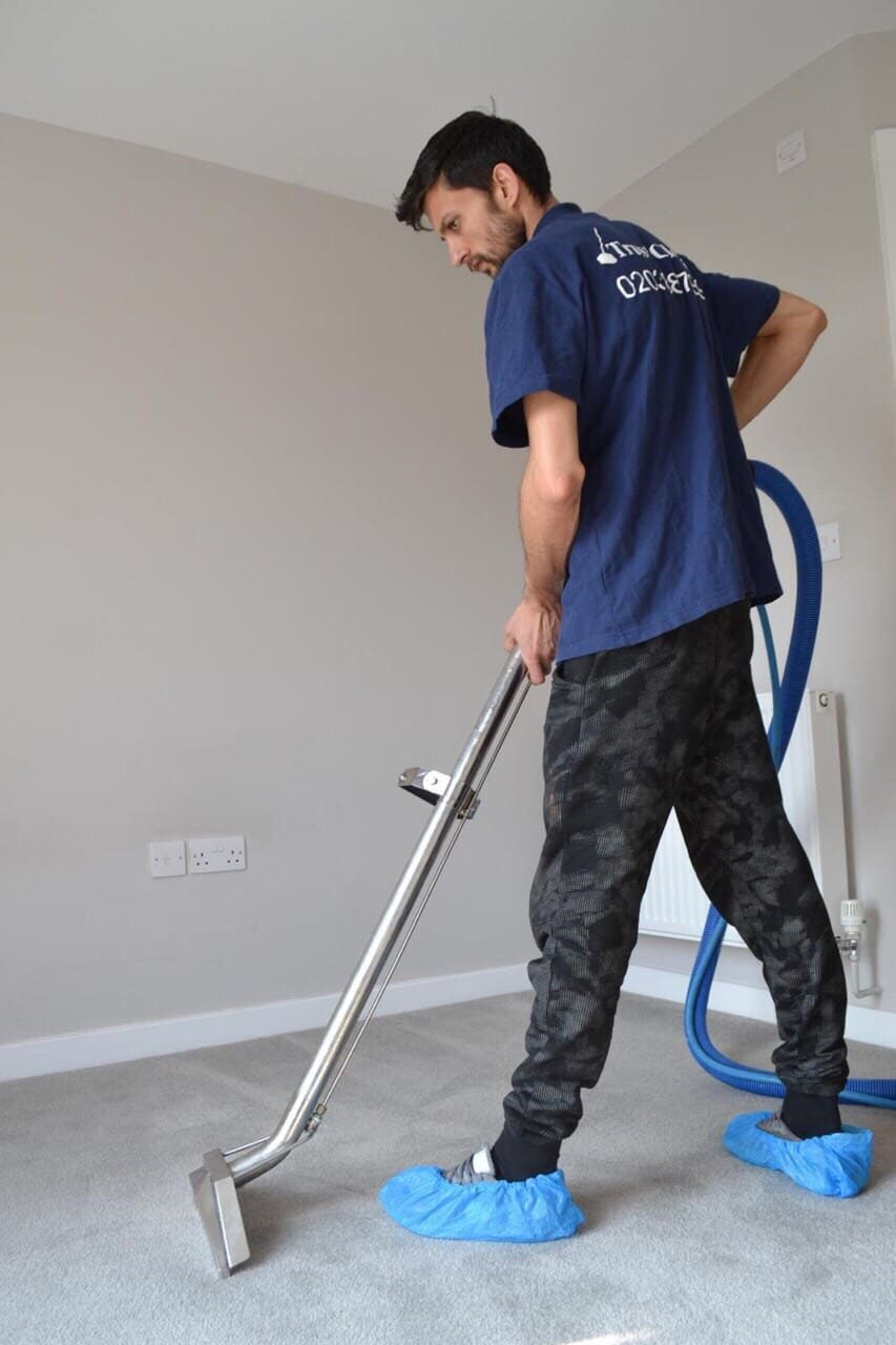 Yang man whit blue t-shirt cleaning carpet in london hose